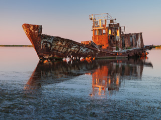last sun lights on the board of ship wreck on shallow at sea in summer day