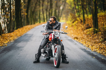 Bearded brutal man in sunglasses and leather jacket sitting on a motorcycle on the road in the forest
