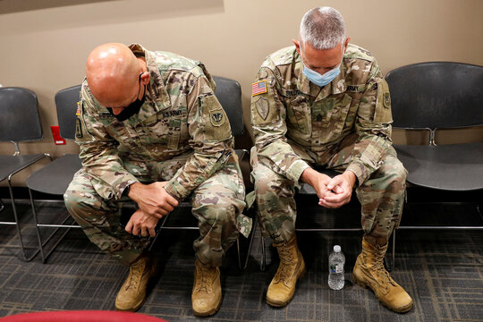 Members of the Wisconsin National Guard bow their heads in prayer at the start of a news conference in Kenosha, Wisconsin