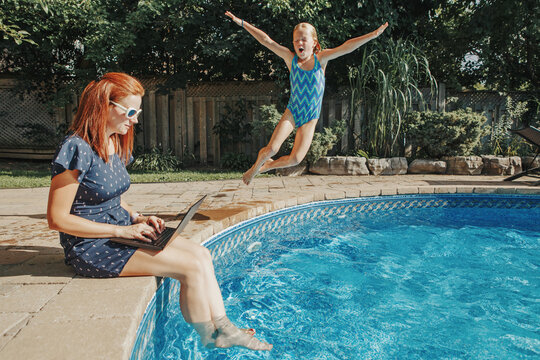 Work from home with kids children. Mother working on laptop by swimming pool. Child daughter jumping in water. Funny family moments. New normal workaction at coronavirus quarantine.