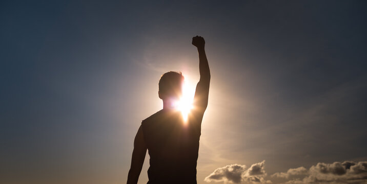 Young strong man with fist up to the sky feeling empowered, and determined.