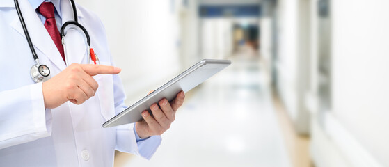 A side view of a male doctor using a tablet at the hospital.