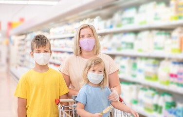 Young woman and her kids wearing protective face masks shop a food at a supermarket during the coronavirus epidemic or flu outbreak