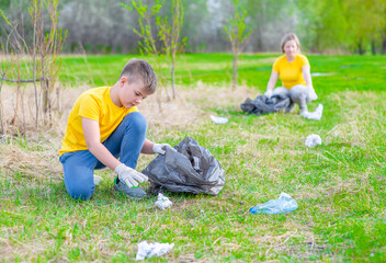 Group of a volunteers scavenges garbage in the summer park. Volunteer and ecology concept