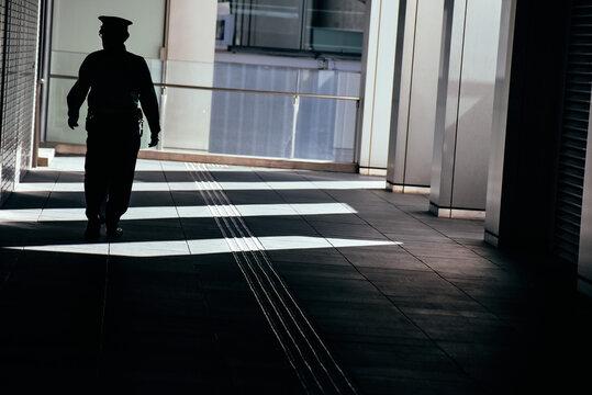 光射し込む歩道を歩く人
