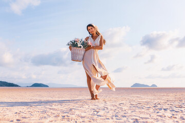 beautiful young stylish woman with basket with flowers outdoors at sunset