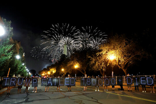 Donald Trump campaign fireworks explode behind the Washington Monument as demonstrators hold signs during a protest in Washington