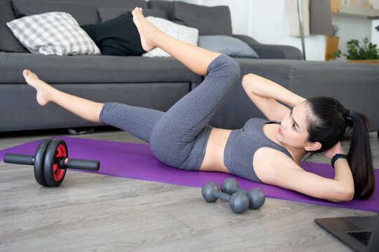 Fitness woman is doing abs workout with exercising crunches on a mat, Healthy lifestyle and sports concept