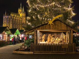 Erfurt, Germany. Nativity scene with 14 wooden figures under the Christmas tree at Christmas market on Cathedral Square in night. St Mary's Cathedral is visible in the background.