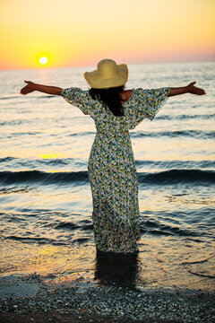 Back of woman with open arms to the sun