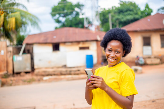 excited black African millennial girl with afro haired using modern smartphone checking social media chatting with friends