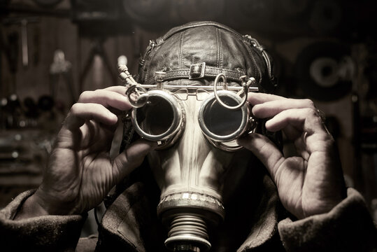 A man in a respirator and glasses in the style of steampunk, dressed in an overcoat.
