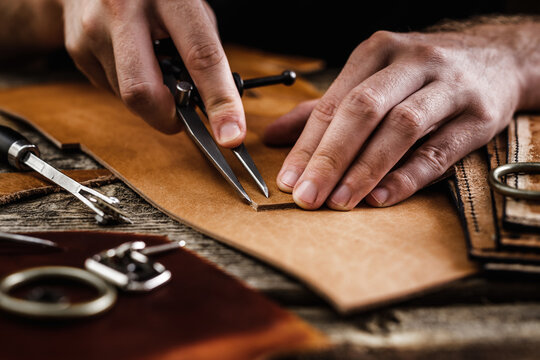Close up of a shoemaker or artisan worker hands. Leather craft tools on old wood table. Leather craft workshop.