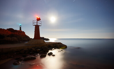 Two lighthouses at night on the breakwater with the lights on and the moon in the background