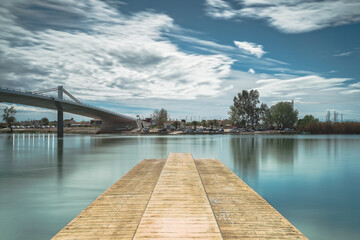 Large wooden pier of a river next to a bridge with the landscape reflected in the water
