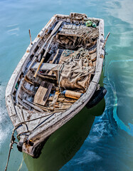 Old fishing boat moored in the harbor with oil-stained sea water