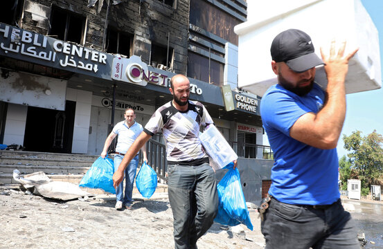 People walk as they hold plastic bags and boxes near damaged shops in the aftermath of clashes in Khaldeh