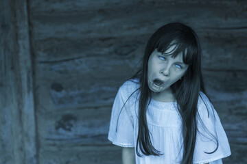 Scary ghost halloween theme. Horror devil girl with white eyes opens mouth and shouts
