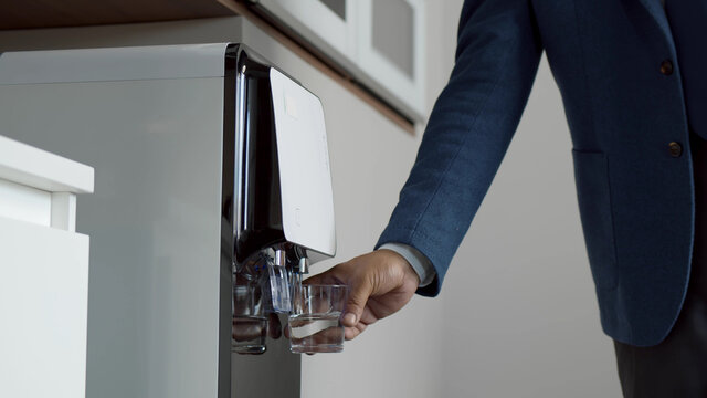 Close up of businessman hand pouring water from cooler in kitchen