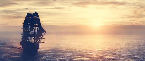 Fototapeta Pirate ship sailing on the ocean at sunset