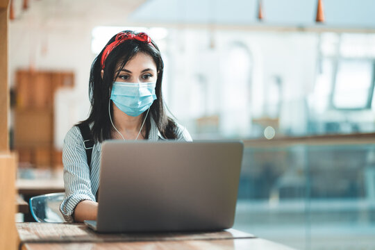 Young woman using a laptop wearing a protective face mask and studying in a university library