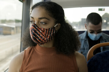 Young adult afro American woman sitting on the bus wearing face mask during coronavirus pandemic