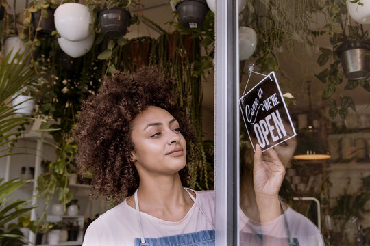 African American small business store owner opening up plant shop