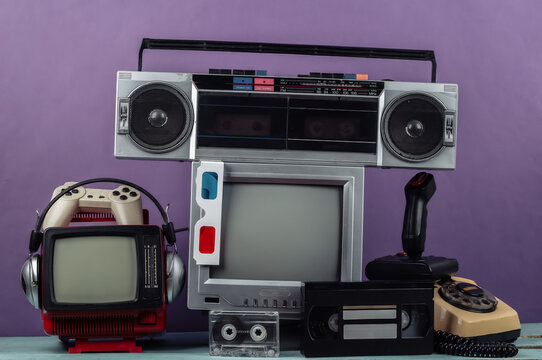 Retro portable mini tv set,  radio receiver, record player, headphones, joystick, 3d glasses, gamepad, audio and video cassette, phone on purple background. Attributes 80s, retro media, entertainment