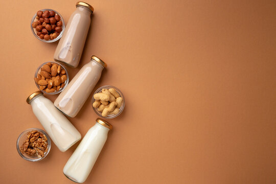 Bottles of nut non dairy milk on brown background flatlay