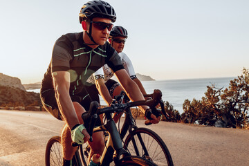 Two professional male cyclists riding their racing bicycles in the morning together Fotobehang