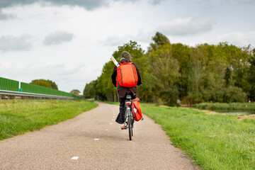 A lonely biker with a backpack near the A44 highway in the south-Holland village of Sassenheim in the Netherlands.