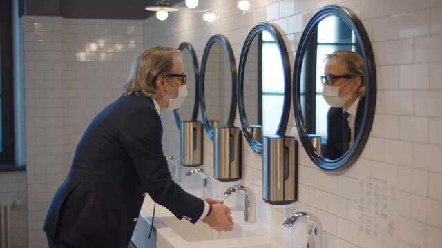 Senior businessman wearing safety mask washing hands in public restroom