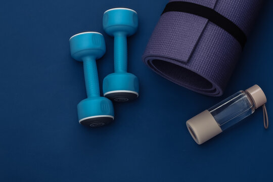 Dumbbells, fitness mat and water bottle on classic blue background. Healthy lifestyle, fitness training. Color 2020. Top view. Flat lay