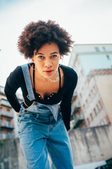 Stylish cool black woman dancing outdoor - confident black woman posing outdoor - pride, girl power, body pisitive concept