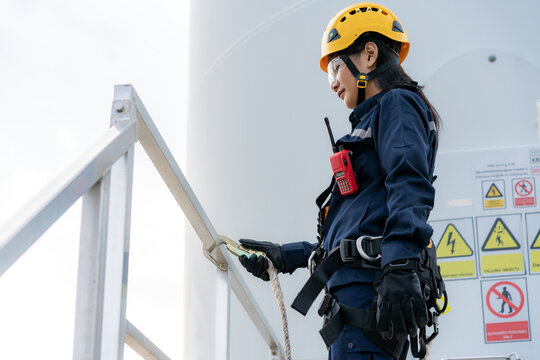 Asian woman Inspection engineer wearing safety harness and safety line working preparing and progress check of a wind turbine with safety in wind farm in Thailand.