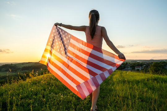 Happy young woman posing with USA national flag standing outdoors at sunset. Positive girl celebrating United States independence day. International day of democracy concept.