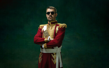 Fototapeta Wearing stylish eyewear. Young man in suit as Nicholas II isolated on dark green background. Retro style, comparison of eras concept. Beautiful male model like historical character, monarch, old obraz