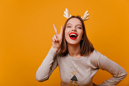 An enthusiastic, funny, young, perky girl 25 years old smiles into the camera and shows a peace sign with two hands near her face. Photo in studio on an orange background.