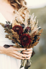 Wedding bouquet in boho style on the background of nature. The bride holds a bouquet of dried flowers.