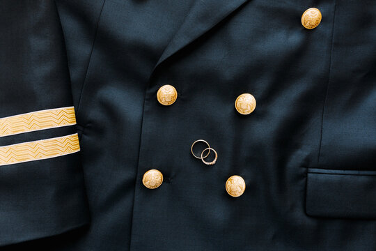 Top view of two gold wedding rings on a black mens blazer with buttons with a two-headed eagle.