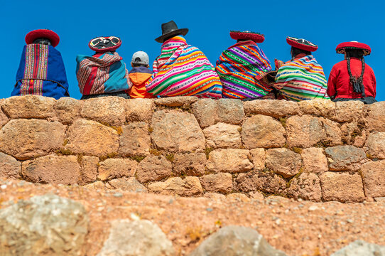 A group of Quechua indigenous women in traditional clothing with a boy sitting on an ancient Inca wall, Chinchero, Cusco, Peru.