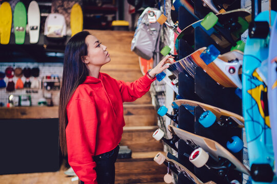 Side view of attractive teenage woman choosing longboard from store rack during Black Friday sales, beautiful Japanese hipster girl spending day for buying skateboard and practicing hobby skills