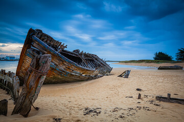 Old shipwrecks at the ship cemetary at river Etel in Brittany, France
