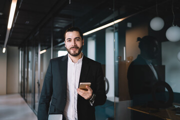Businessman standing with smartphone in hand