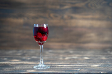 Homemade tincture of red cherry. Berry alcoholic drinks concept. Homemade red wine made from ripe cherries in wineglass on wooden background, Ukraine