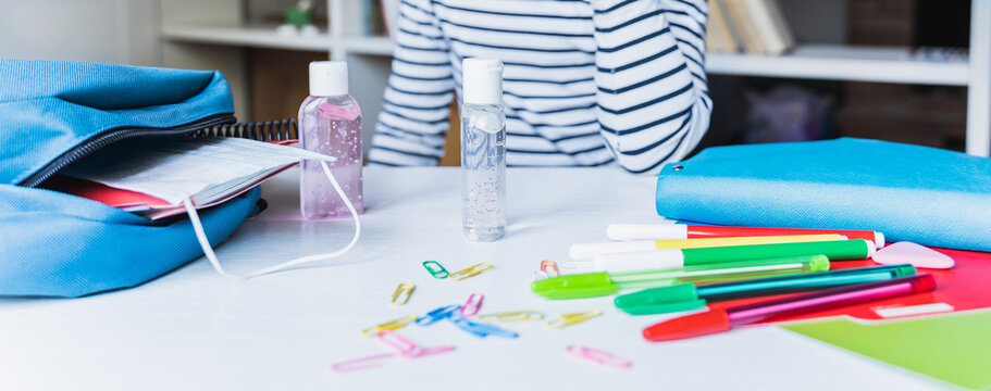 Little girl packing blue backpack in kids's room. Face mask, bottle of sanitizer, stationery, pens, multicolored markers, notebooks. Back to school. Mom's hygiene,safety precautions after coronavirus