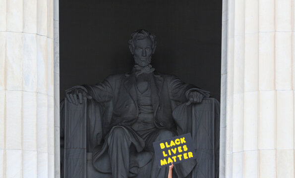 """Demonstrator holds up Black Lives Matter sign in front of Lincoln Memorial at the """"Get Your Knee Off Our Necks"""" Commitment March on Washington 2020 in Washington"""