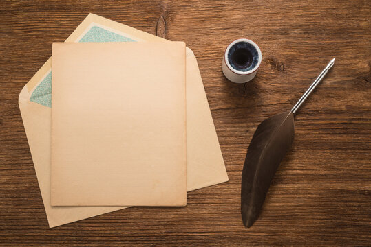Envelope, goose feather, inkwell on a wood table