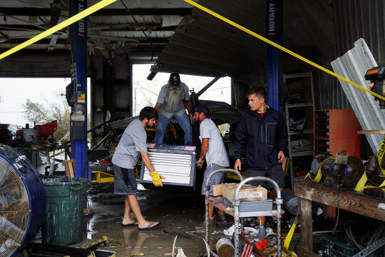 Family and friends help Brent Morvant clean up his paint and body shop after Hurricane Laura passed through the area in Cameron Parish