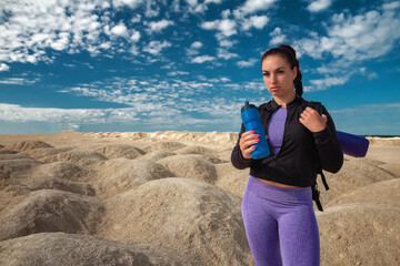 young woman half-face one tourist on hilly area in sportswear and with backpack drinks water on sunny day, copy space